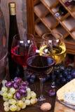 红色、玫瑰色和白色玻璃和瓶酒 葡萄、坚果、乳酪和老木桶 库存照片