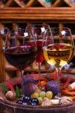 红色、玫瑰色和白色玻璃和瓶酒 葡萄、无花果、坚果和叶子在老木桶 免版税库存图片