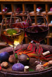 红色、玫瑰色和白色玻璃和瓶酒 葡萄、无花果、坚果和叶子在老木桶 库存图片