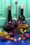 红色、玫瑰色和白色玻璃和瓶酒 葡萄、无花果、坚果和叶子在老蓝色桌上 库存图片
