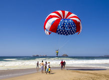 红色、美国国旗parasail白色和蓝色反对明亮的蓝天的 图库摄影