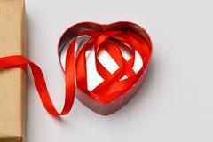 红色上升了 以心脏的形式箱子在灰色背景说谎和在它放置从箱子的一条红色丝带 库存图片