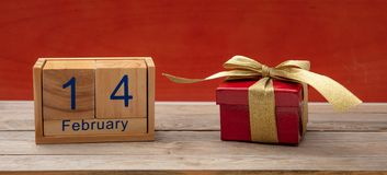红色上升了 日历木立方体、2月14日和一个礼物盒在木桌,红色墙壁上 免版税库存照片