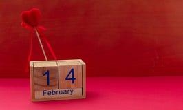 红色上升了 2月14日和红色天鹅绒心脏在红色背景 库存照片