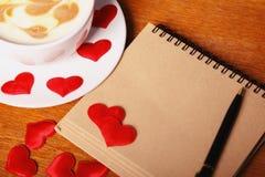 红色上升了 有拿铁艺术的热奶咖啡杯以心脏、一个老纸笔记本和一支笔的形式在一张木桌上 库存照片