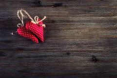 红色上升了 红色在木背景的布料手工制造心脏 免版税图库摄影