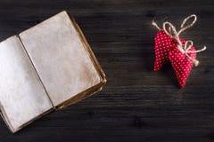 红色上升了 红色布料手工制造心脏和老开放书在木背景 库存图片