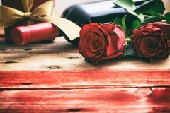 红色上升了 红葡萄酒瓶、玫瑰和一件礼物在木背景 库存图片
