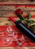 红色上升了 红葡萄酒瓶、玻璃和一朵玫瑰在红色木背景 免版税图库摄影