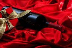 红色上升了 红葡萄酒瓶和一件礼物在红色缎 免版税库存图片