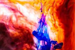红色上色了抽象下落云彩丙烯酸酯的下面水性涂料背景黄色蓝绿色橙色波斯菊黑色抽象天空海温泉 免版税图库摄影
