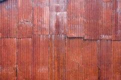 红色与铁锈的金属波纹状的房屋板壁 免版税库存照片