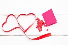 红色丝带和在白色木背景的贺卡的两心脏与一些小心脏的 免版税图库摄影