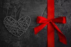 红色丝带和心脏在黑暗的背景 圣华伦泰` s天和婚礼的题材 图库摄影