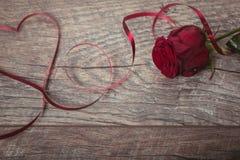 红色丝带在一张黑暗的木桌上的形状心脏被排行 情人节背景,土气样式 情人节桌p 库存照片