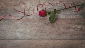 红色丝带在一张黑暗的木桌上的形状心脏被排行 情人节背景,土气样式 情人节桌p 库存图片