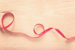 红色丝带小条在木背景的 免版税图库摄影