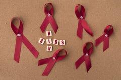 红色丝带援助与AIDS/HIV词的丝带在布告牌 库存照片