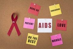红色丝带援助在布告牌的丝带有鼓励的话的助手/艾滋病毒携带者的 免版税库存照片