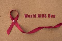 红色丝带援助在布告牌的丝带有`世界援助天`词的 库存照片