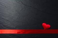红色丝带磁带和心脏在石背景 免版税库存照片