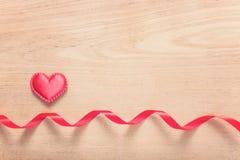 红色丝带红色心脏和小条在木背景的 免版税库存图片