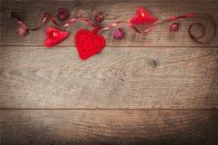 红色丝带,以心脏的形式蜡烛在一张黑暗的木桌上 情人节背景,土气样式 免版税库存图片