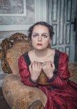红色中世纪礼服的美丽的妇女在扶手椅子 免版税库存照片