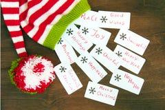 红色五颜六色的圣诞节,白色和绿色在p编织了圣诞老人帮手帽子,自然羊毛,手工制造编织,与圣诞节祝愿 库存图片