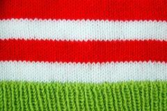 红色五颜六色的圣诞节,白色和绿色编织了圣诞老人帮手帽子的样式 库存照片