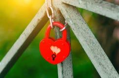 红色以心脏的形式婚礼闭合的锁 城堡介入在蓝天背景的一座桥梁在一个明亮的晴天 库存图片