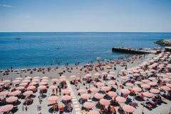 红色伞和游人节奏一个晴朗的海滩的在热那亚,意大利 库存图片