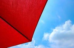 红色伞和蓝天在晴天 免版税库存照片
