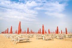 红色伞和sunbeds在里米尼使-意大利夏天靠岸 免版税库存照片