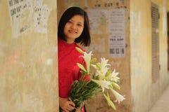 红色传统礼服的美女带来圣母百合花在她的手上 免版税图库摄影