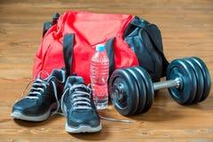 红色体育在一个重的哑铃附近请求和运动鞋 库存图片