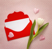 红色信封和白色郁金香在桃红色背景 文本的空间 图库摄影
