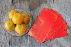 红色信封小包顶视图或ang爪子和桔子在一个碗在老木背景 春节节日概念 免版税库存图片