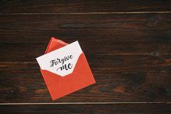 红色信封顶视图与原谅我在纸的字法 免版税库存照片