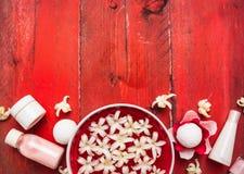 红色健康背景:在水中滚保龄球与白花,奶油和化妆水瓶在红色木桌上 免版税图库摄影