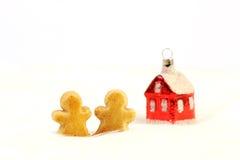 红色光滑的圣诞节装饰-一点的房子和站立两个姜饼的形象在白色毛皮背景 库存图片