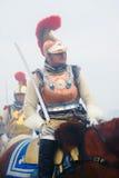 红色全身羽毛装饰的金黄盔甲的人 库存照片