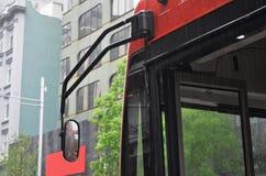 红色公共汽车前面在sideview的,当下雨时 免版税库存照片