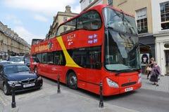 红色公共汽车在巴恩英国搭载乘客 免版税库存图片