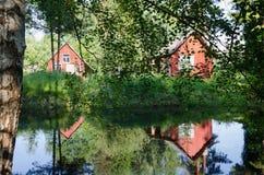 红色农村家通过在池塘的分支反射了 库存图片