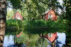 红色农村家通过在池塘的分支反射了 库存照片