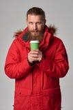 红色冬天夹克的人有杯子的热的饮料 免版税库存照片