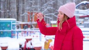 红色冬天夹克的画象逗人喜爱的年轻女人拿着束花揪和打击雪 股票录像