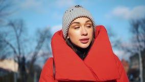 红色冬天夹克的美丽的妇女沿用雪盖的街道走在一个美丽的老欧洲城市 股票视频
