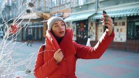 红色冬天夹克的迷人的女孩在一明亮的天采取在她的站立在冬天街道上的电话的selfie 影视素材